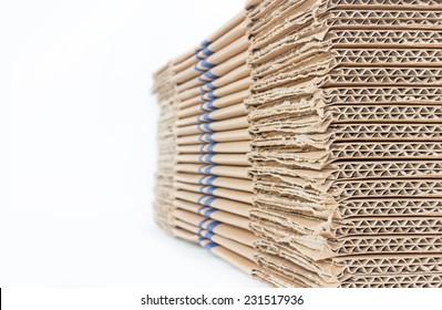 Stacked brown corrugated cardboard boxes isolated on white background with copy space. Side and edge perspective view of flattened boxes. Nice for new packaging or recycling idea.