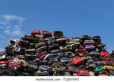 Stacked cars at a junkyard in a blue sky.