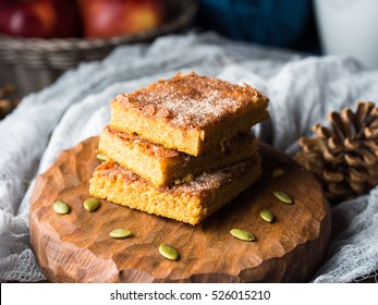 Stacked Christmas spiced pumpkin blondies topped with sugar and cinnamon. Baked square bar treat for winter breakfast. Sweet food still life on dark background