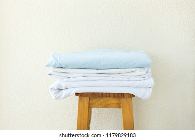 Stacked clean folded cotton bedlinen on wooden stool white wall background. Laundry washing cleanliness concept. Provence Mediterranean nordic interior. Poster banner with copy space