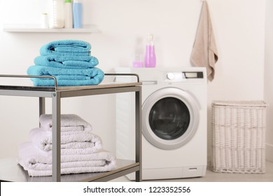 Stacked clean soft towels on table in laundry room. Space for text