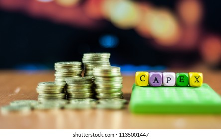 stacked coins and alphabet dices with text CAPEX. CAPEX stand for capital expenditure.