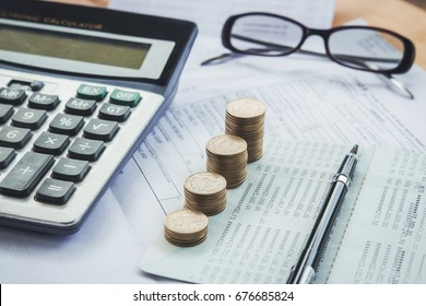 Stacked of Coins with calculator,Bank account,tax form,glasses and pen,Income Tax Raise Concept
