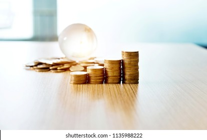 Stacked coins and glass globe on table.