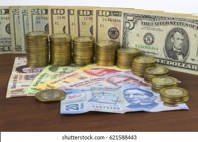Stacked coins and Mexican banknotes with United States bills of america background
