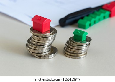 Stacked coins with miniature house.