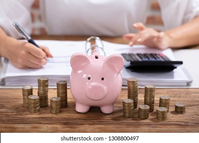 Stacked Coins And Pink Piggy Bank In Front Of Businesswoman Calculating Invoice On Wooden Desk