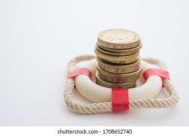 Stacked coins in red lifebuoy or lifebelt with white background copy space. Assets wealth, money saving or money investment protection and security by insurance concept. Risk management analysis.