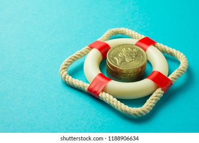 Stacked coins surrounded by lifebuoy or lifebelt on blue background. Concept economy of safety business financial, insurance, investment, risk management, money saving and wealth asset protection