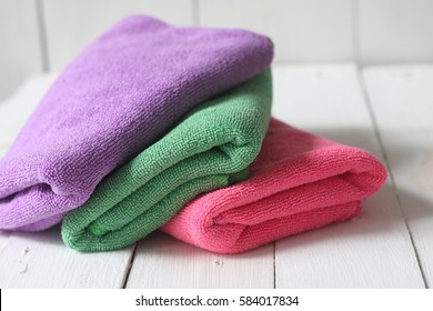 Stacked of colorful microfiber kitchen towels on white wooden palette
