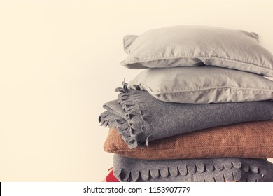 stacked colorful pillows cushion plaid linen textile wooden chair near white wall pile concept elements interior objects isolated on white. closeup country style retro toning beige