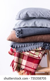 stacked colorful pillows cushion plaid linen textile wooden chair near white wall pile concept