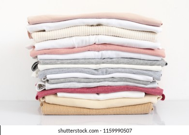 Stacked colorful t-shirts on white background.