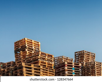 Stacked up colorful wooden cargo pallets against a blue sky