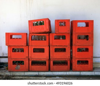 Stacked crates of bottles inside red plastic crates against a white wall