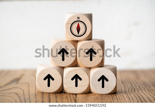 stacked cubes on wooden background with a compass symbol on top symbolizing to organize a team to a common goal