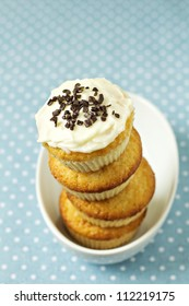 Stacked cupcakes in a bowl with frosting on top