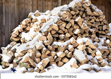stacked firewood covered in snow