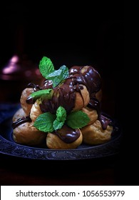 Stacked fresh dairy cream filled chocolate profiteroles with fresh mont garnish shot against a black background with selective focus. Copy space. The perfect image for your dessert menu cover design.