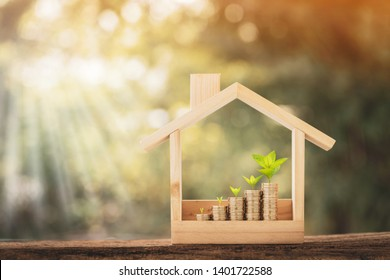 Stacked gold coins and plant growing on the top put in the wooden home model on the wood on bokeh background in the public park, Business investment and loans for real estate concept.
