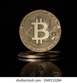 Stacked golden bitcoins coins for BTC cryptocurrency on a black reflective surface background