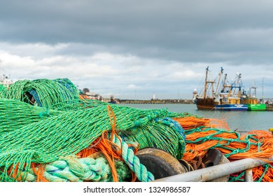 Stacked green and orange coloured fishing nets with fishing boats in the background docked at Howth Harbour in County Dublin, Ireland.