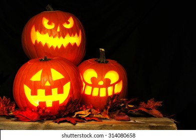 Stacked Halloween Jack o Lanterns illuminated at night with old wood and autumn leaves
