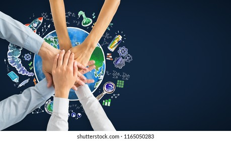 Stacked hands with creative globe and business sketch. Worldwide teamwork and plan concept
