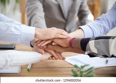 Stacked hands pile close up view, diverse business people holding hands together, coaching training unity concept, sales team corporate connection, engage in teambuilding loyalty, support in teamwork