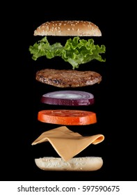Stacked juicy hamburger ingredients isolated on black. Fast food menu cover