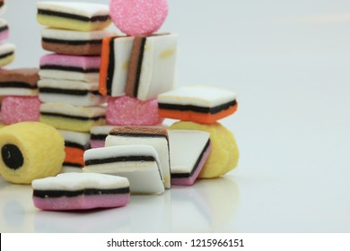 Stacked liquorice allsorts in different shapes, colors and sizes