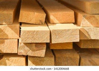 Stacked lumber. Folded wood.Closeup wooden boards.The surface of the end of the board.Lots of planks stacked on top of each other in the warehouse.Lumber for use in construction.