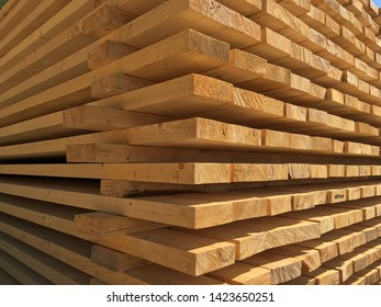 Stacked lumber or timber. Wooden plank stacked for construction or sale.