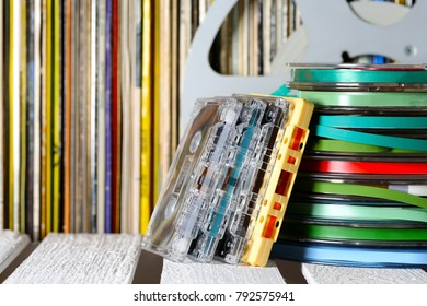 Stacked magnetic tapes and vinyl records on the shelf are visible in a background.