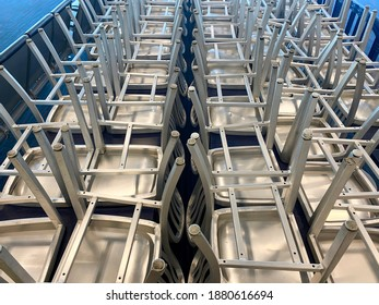 Stacked up metal chairs in rows