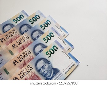 stacked mexican banknotes of 500 pesos in left down corner and white background