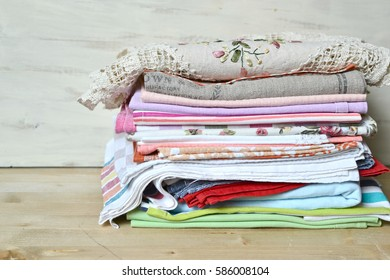 Stacked multicolored table linen on a wooden background