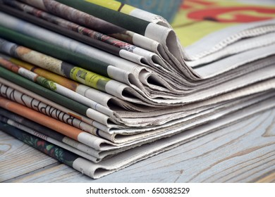 Stacked newspapers on a wooden table background