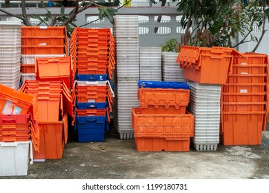 Stacked of old plastic basket and boxes in orange, blue and white color on concrete floor with tree and concrete fence in background