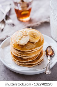 Stacked Pancakes with banana slices and maple syrup
