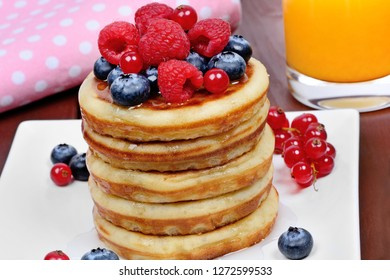 Stacked of pancakes in a plate with fresh berries and orange juice on wooden table