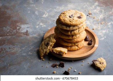 Stacked peanut butter cookies with chocolate chunks on concrete background