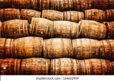Stacked pile of old whisky and wine wooden barrels in vintage style