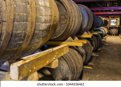 Stacked pile of old wooden barrels and casks in aging cellar at whisky distillery in Scotland.