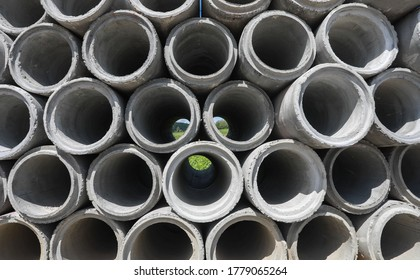 stacked pipe at concrete factory. Stack of concrete drainage pipes for wells and water discharges with blue sky