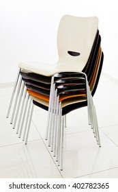 Stacked plastic chairs in white room, side view
