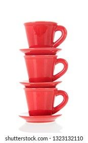 Stacked red cups and saucers isolated over white background