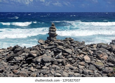 Stacked rocks on a rocky beach with surf