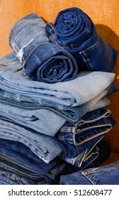 Stacked of rolled jeans stack-wooden board background
