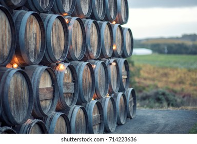 Stacked rustic oak barrels near a vineyard in California wine country